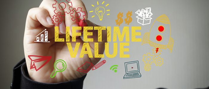 Hand holding pen overlaid by Lifetime Value graphic