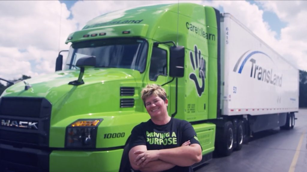 Woman standing in front of semi truck